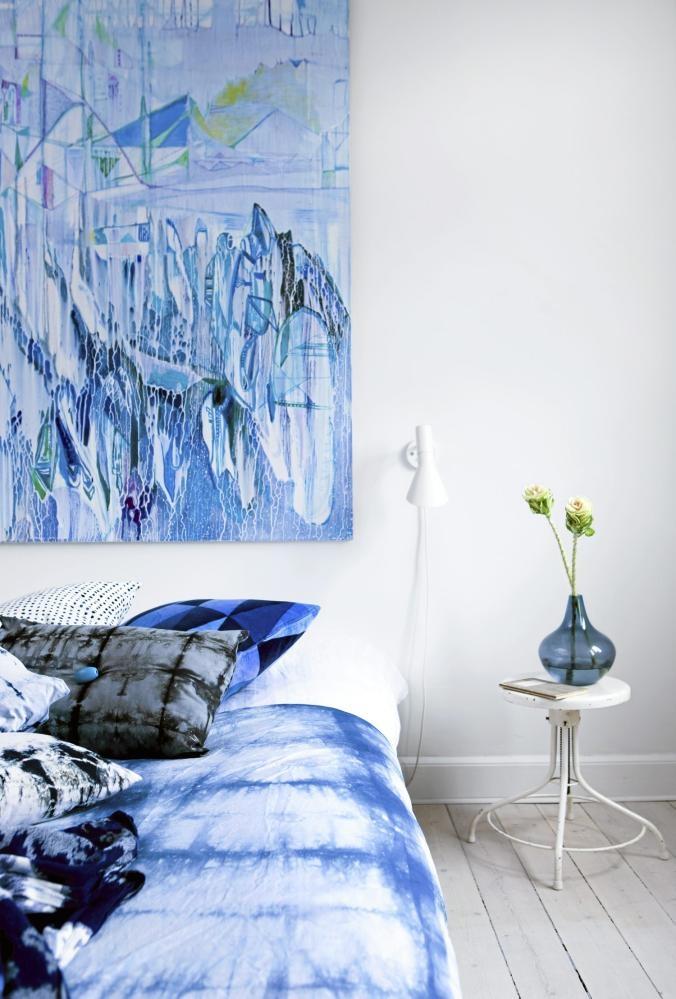 Sengeteppet er laget med såkalt firkantet batikkteknikk. Batikk er ekstra fint med tilbehør i samme farge. Det hvite bordet er egentlig en krakk fra svensklandstil.dk. Den blå vasen er et loppefunn. Maleriet på veggen er av Ida Settergren.