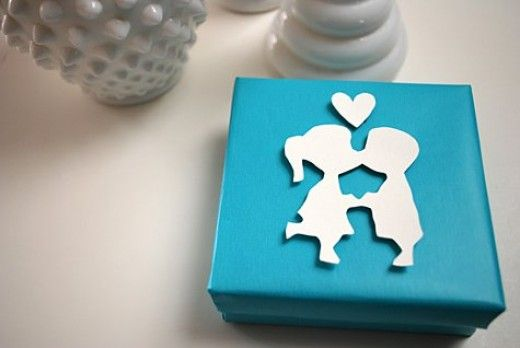 """Larger gift boxes can be embellished with elegant Valentine-themed designs, cut out from card stock. The """"Kissing Couple"""" gift wrap tutorial can be found on MerrimentDesign.com"""