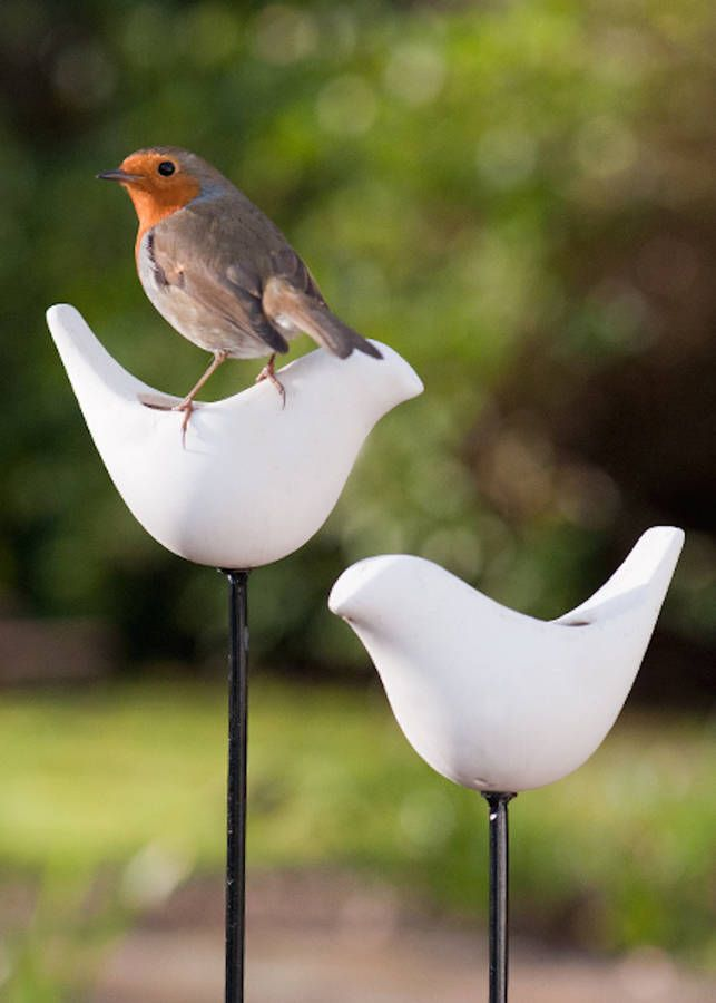 Lovely white garden birdfeeder in bird shape cast in white porcelain mounted a metal pole The porcelain bird screws onto a 1m black metal pole . It comes in a choice of 2 styles - cocked tailed bird or bird in flight. This cute birdfeeder is made from white porcelain and is totally frostproof. Simply fill with your choice of birdseed and watch your feathered friends gather for a feast. The small feeding area discourages larger birds such as pigeons from trying to feed from it allowing the…