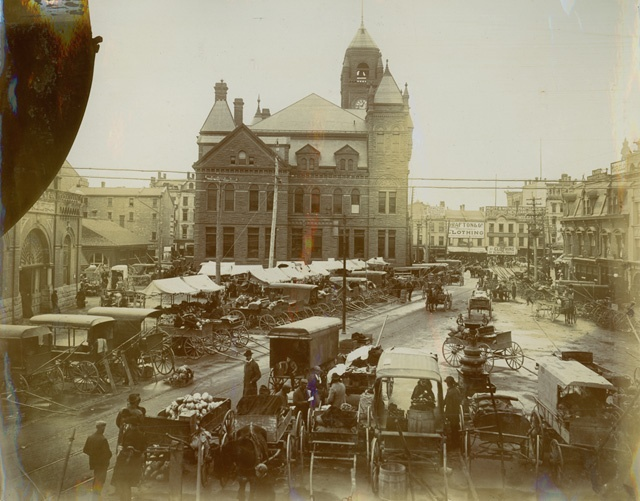 Hamilton Farmers' Market, 1890s. Taken from what is now the middle of Jackson Square facing east towards James St. N. The large building in the center, is old City Hall. To the left is the entrance to Market Hall, which was destroyed by fire in 1917. Photo by Charles S. Cochran.
