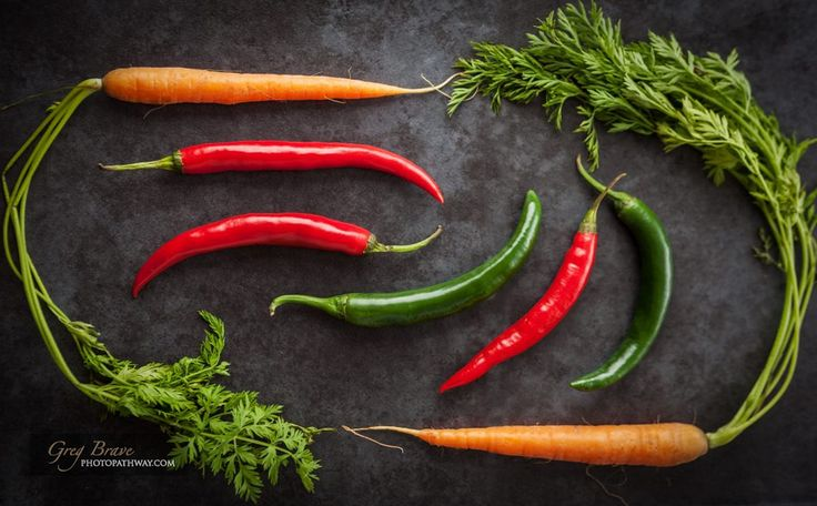 Hot chili peppers and Dutch sweet carrots creatively arranged on grunge background. Top view.