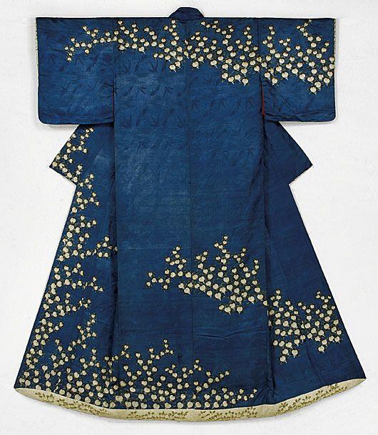 橘模様打掛。江戸後期。 変形の蝶と鳥の地文をもつ繻子を納戸色に染め、橘の群生を白揚して染める。 小袖を改変したもので袷に仕立て綿を入れた裾とする。