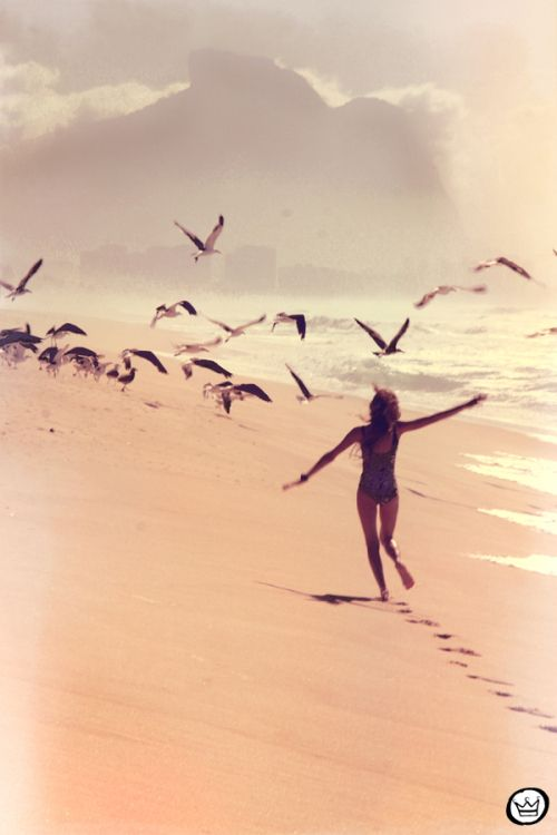 A girl running with birds feeling free. She looks stress free and as if she was flying summer sun