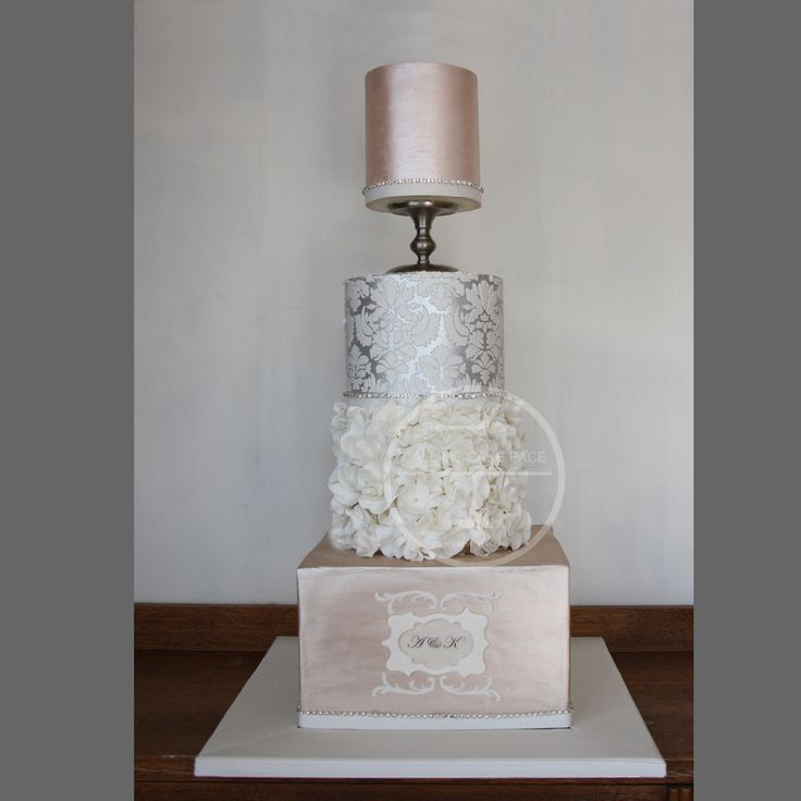 CHAMPAGNE AND SILVER WEDDING CAKE Champagne and silver with damask lace, white Scrunch Roses and hand painted monogram.