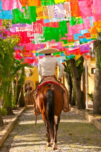 Destination wedding Mexico: Charro with colorful papel picado banners in the background.
