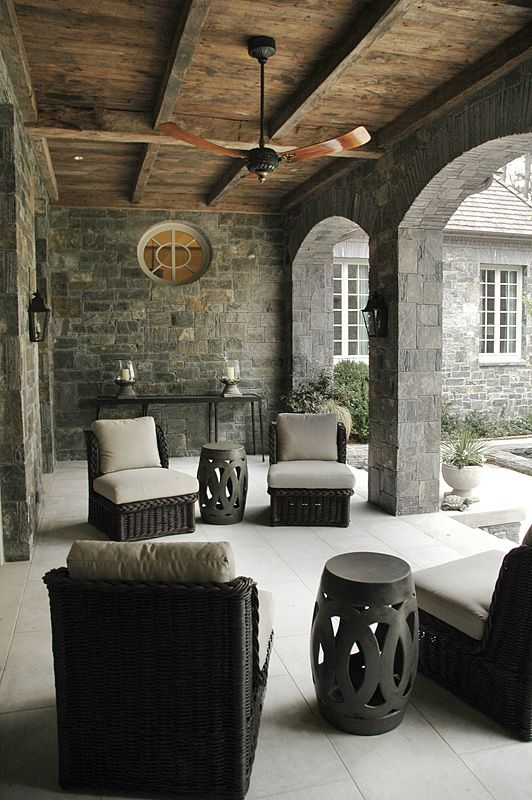 The aged wood ceiling and stone walls create a rustic yet modern feel to this cool sitting area