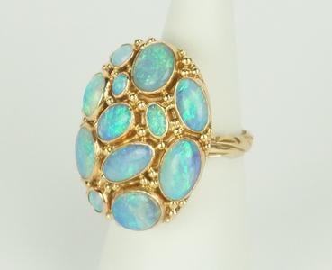 Een 14 krt. geelgouden ring bezet met 12 blauwe opalen, maat 16.5.