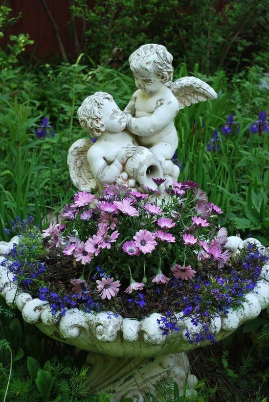 Bird bath holding garden flowers