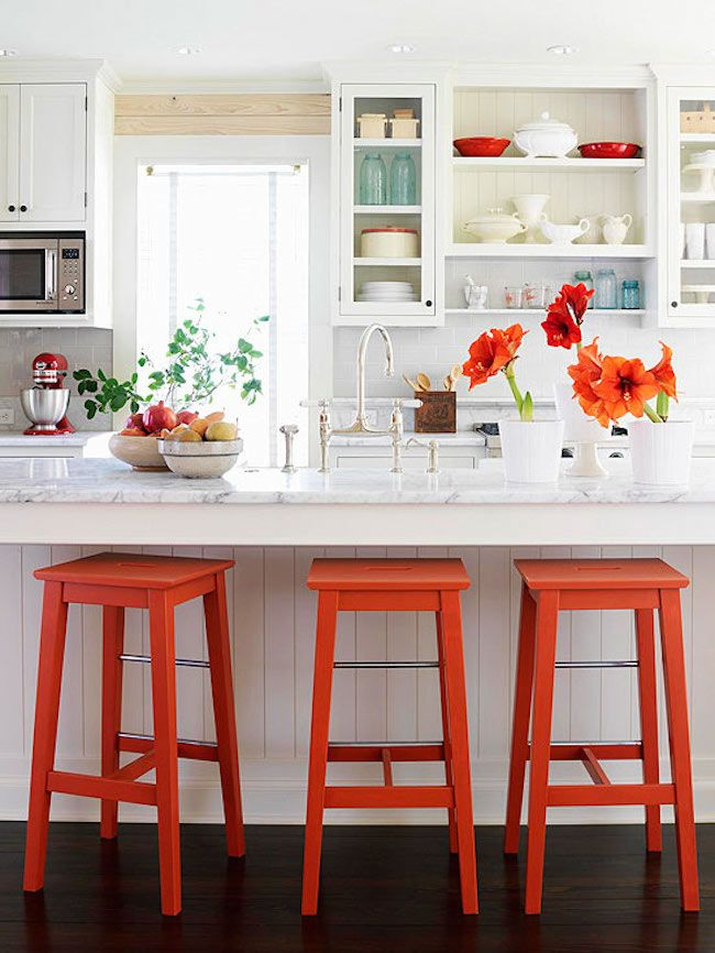 Bright orange bar stools and accents in a white kitchen