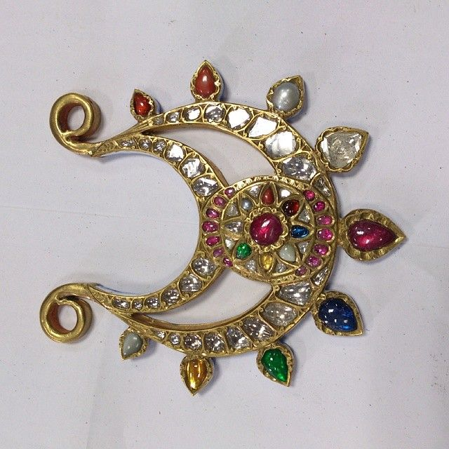 navratna pendant that comprises 9 gems where the ruby takes the centre of the settings, being the queen of gems. Description by Pinner Mahua Roy Chowdhury