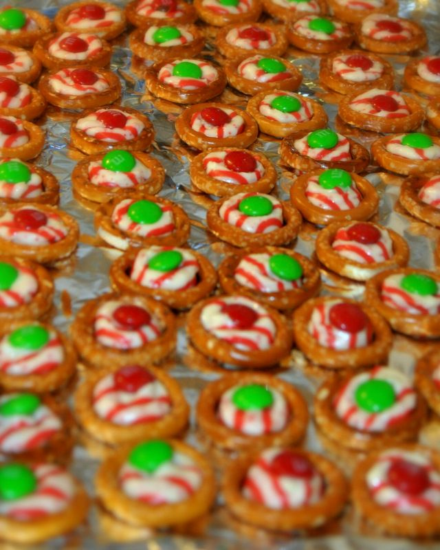 Easiest treat EVER. Pretzel with mint Kiss (or Rolo/Caramel Kiss) topped with red or green M