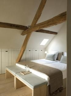 idee sfeer. wit dak, houten spant en kasten in knieschot verwerkt.