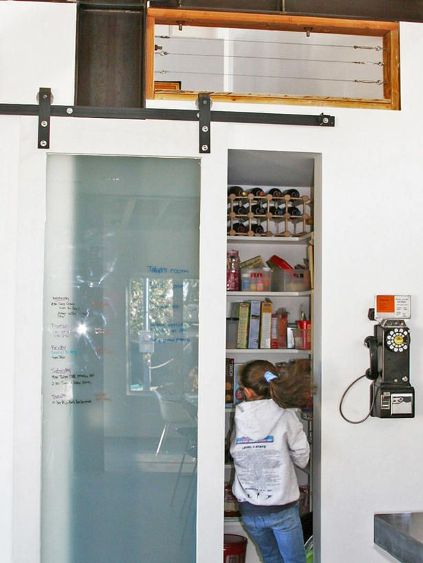 Multipurpose Pantry Door The sliding-glass barn door on exposed tracks used for this kitchen pantry does double-duty as a message board. Grocery lists and family notes can be written right on the glass.