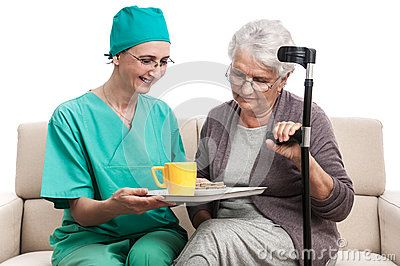 A smiling and confident female nurse giving a cup of tea to an old disabled woman. Senior having meal in hospital. Isolated on white.