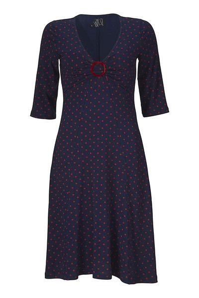 Pippa kjole fra WEIZ Copenhagen har et utrolig smuk snit, der både slanker og forlænger kroppen. Ved brystet sidder et rødt dasie spænde.
