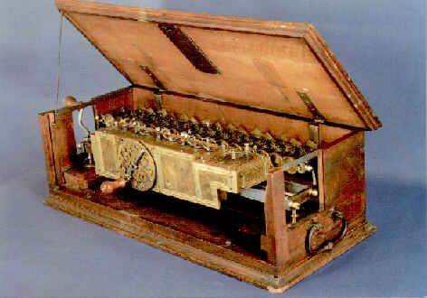 The Staffelwalze, or Stepped Reckoner, a digital calculating machine invented by Gottfried Wilhelm Leibniz around 1672 and built around 1700, on display in the Technische Sammlungen museum in Dresden, Germany. It was the first known calculator that could perform all four arithmetic operations; addition, subtraction, multiplication and division. 67 cm (26 inches) long. The cover plate of the rear section is off to show the wheels of the 16 digit accumulator. Only two machines were made.