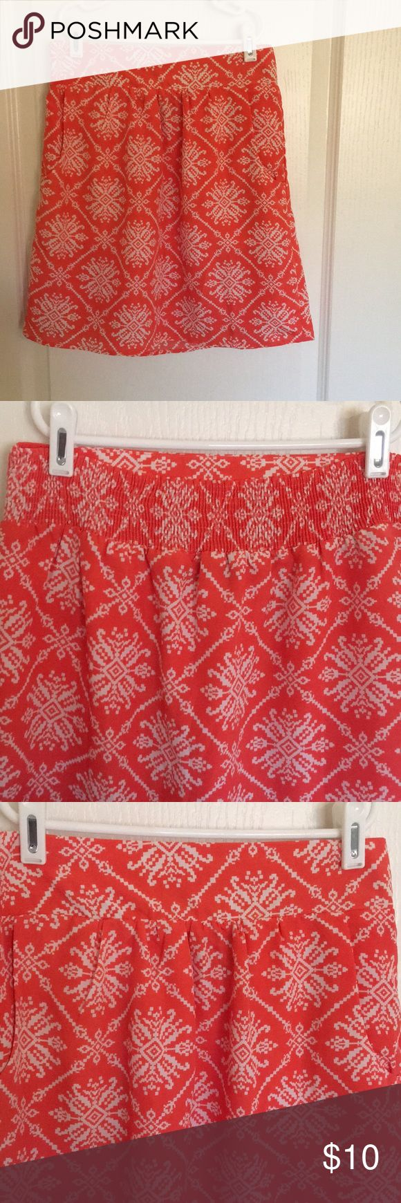 Printed Skirt with Pockets This skirt has a fun print with pockets. It has a wide waistband with elastic back. It is great to pair with a T-shirt and Sanders for a casual look. The color is a peach color with an orange tone. Paraella Skirts Mini