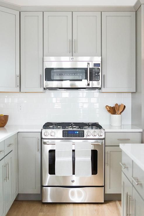 Gorgeous kitchen features pale grey shaker cabinets paired with white quartz countertops and a white subway tiled backsplash.
