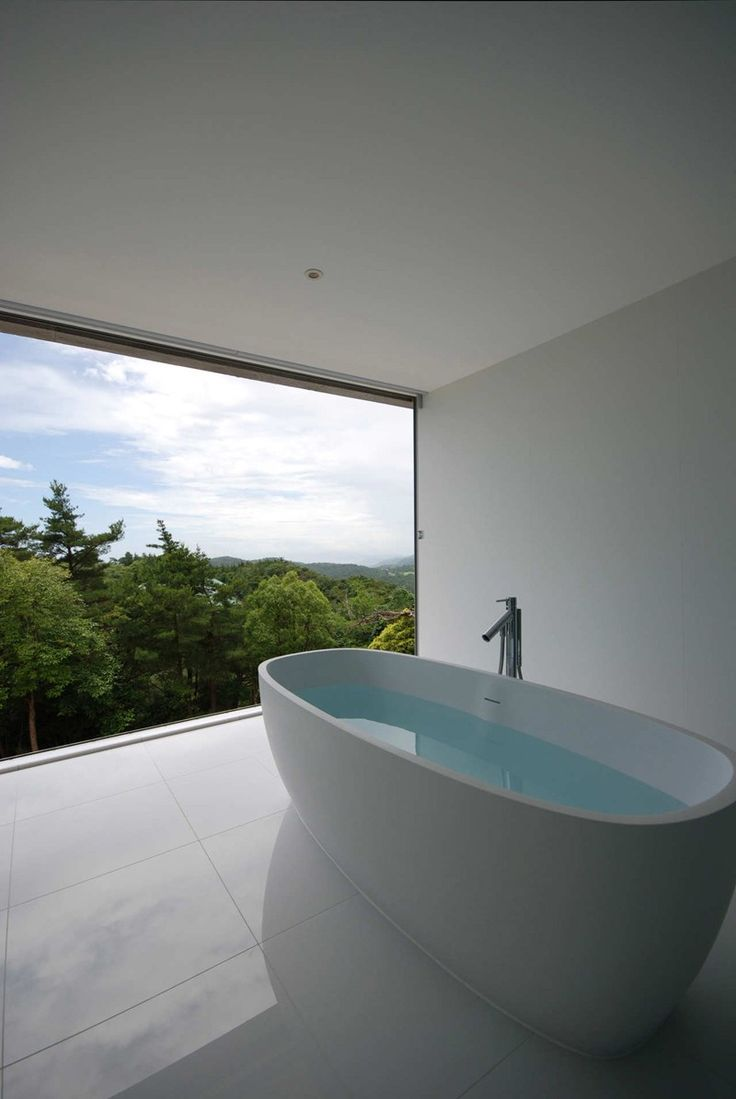 Shinichi Ogawa & Associates gave this minimalist white bathroom a view overlooking the forest surrounding this home in Hyogo, Japan.