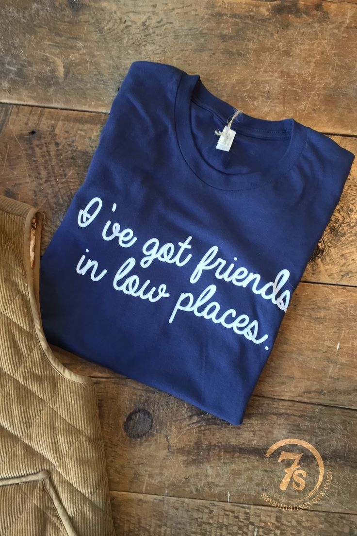 "- ""I've got friends in low places"" graphic t-shirt - Classic Garth Brooks lyrics - White graphics on navy shirt - Great felling soft fit - Adult unisex size t-shirt - Fits true to size - Shown styled"