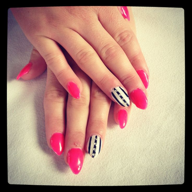 Bright pink pointy gel nails with a black and white stripy nail and gems