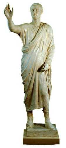 Statua di Aulo Metello, I secolo a.C.Statua in bronzo, a tutto tondo. Da Sanguineto,rive lago Trasimeno.Oggi conservato presso  Firenze, Museo Archeologico.