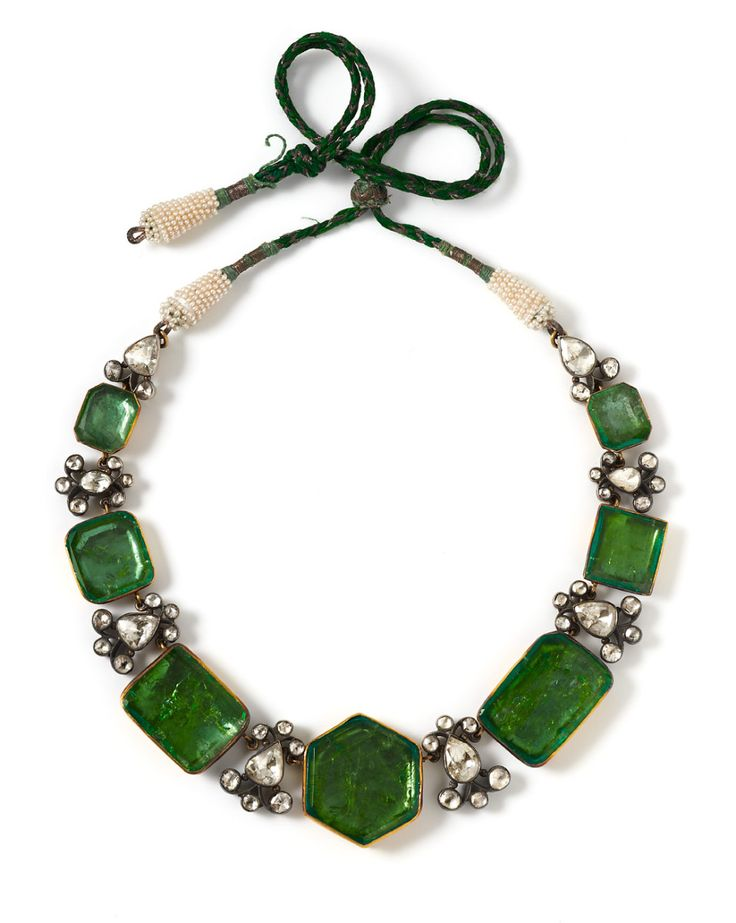 Royal Indian Necklace with seven foiled emeralds in closed gold settings,  separated by diamond clusters in closed silver settings. The cord ends are  wrapped ...