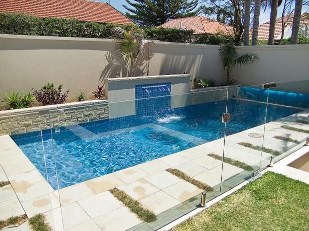 Rectangle Pool With Water Feature a long, rectangular plunge pool with a center blue themed fountain