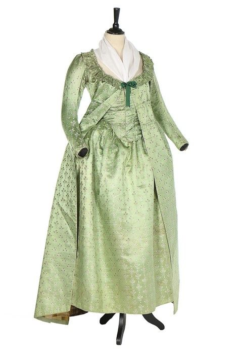 Pregnancy robe, 1790s. Pale green silk sprigged overall with ivory and peach trefoils tied with tassels. Comprising: petticoat with waist ties and two matching bodices, one high fashion (for earlx pregnancy) in 'pierrot' style cut low and tight with closed front, faux waistcoat panels, lined in striped silk. The other in open-robe form with inner boned closed front panels and loose deshabillé-like outer panels, lined in patches of tartan and striped silk.