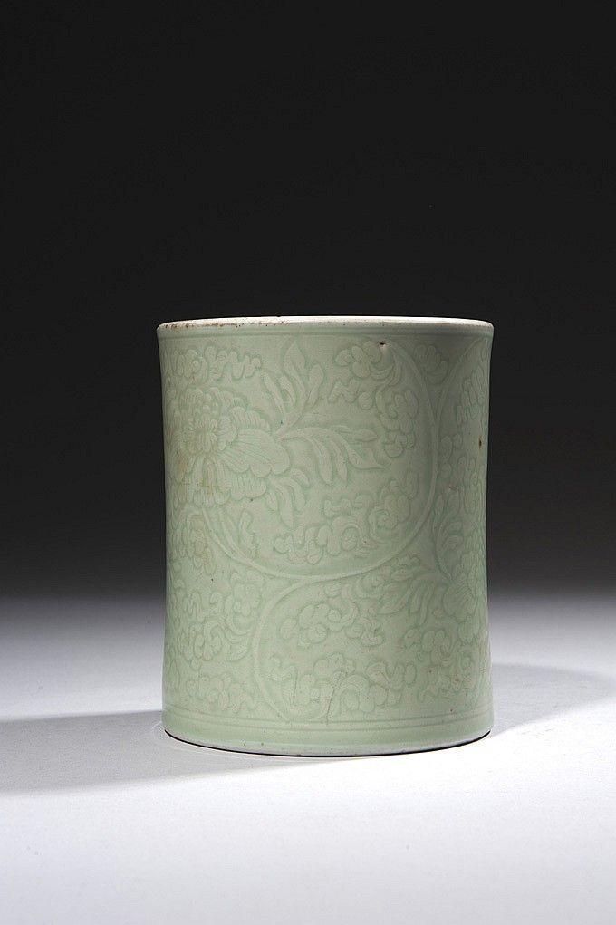"""CHINE Époque KANGXI (1662-1722)  Porte-pinceaux """"bitong"""" en porcelaine émaillée céladon à décor incisé sous la couverte de pivoines dans leur feuillage.  Socle en bois. Hauteur : 15 cm Ébréchures à la base Provenance : Antiquaire Vanderstraten - Bruxelles, le 31 décembre 1941 CHINA - KANGXI Period (1662-1722) A celadon glazed and incised brushpot."""