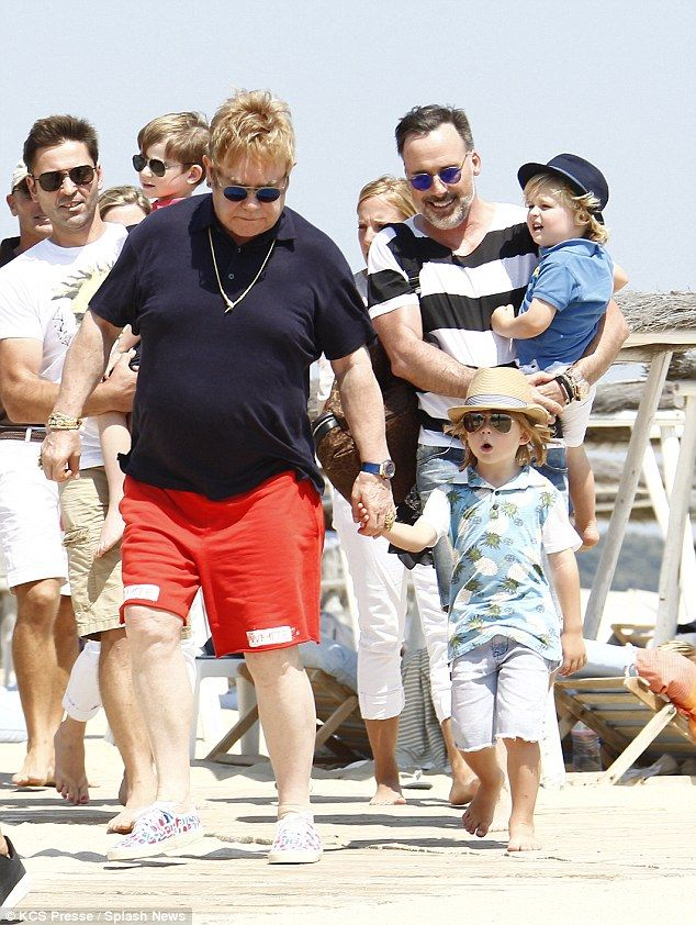 Family affair: Elton and David clutched their boys tightly as they hit the sands...