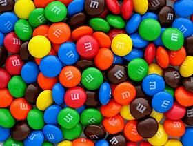 """M&M's (styled as m&m's, pronounced emenems) are """"colorful button-shaped chocolates""""[1] produced by Mars, Incorporated. The candy shell, each of which has the letter """"m"""" printed in lower case on one side, surrounds a filling which varies depending upon the variety of M&M's. The original candy had a milk chocolate filling which, upon introducing other variations, was branded as the """"plain"""" variety. """"Peanut"""" M&M's, which feature a peanut coated in milk chocolate, and finally a candy shell, were…"""