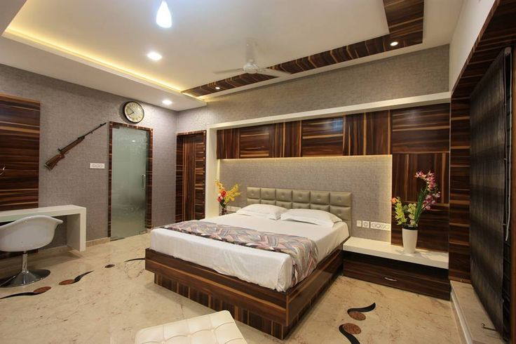 Wooden panelling and wall paper finishes highlights the bed area in son's bedroom.