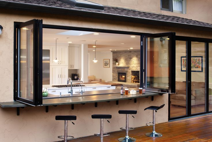 Bi-folding window>door. Window section above kitchen worktops and sink, doors in the dining area