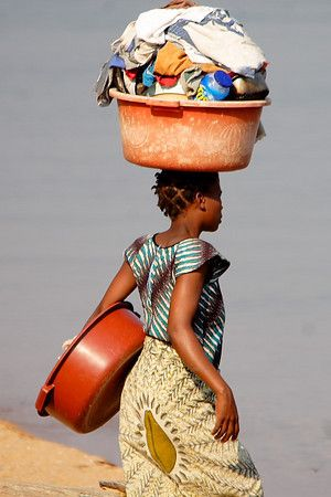 Africa | A girl in Malawi heading down to the lake to do the washing |
