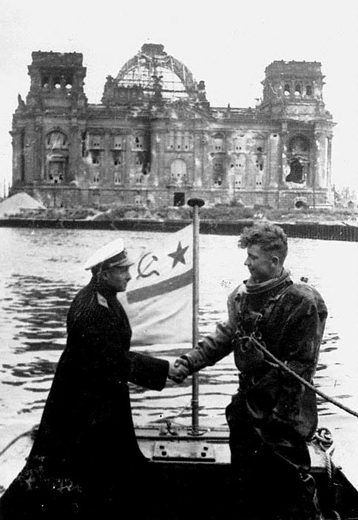 1945, Allemagne, Berlin, Un officier supérieur russe félicite un plongeur chargé de déminer la rivière Spree. Derrière, le Reichstag La légende d'origine faisait état du contre-amiral Ivanovitch Krylov. Je n'ai rien trouvé pour étayer cette hypothèse.
