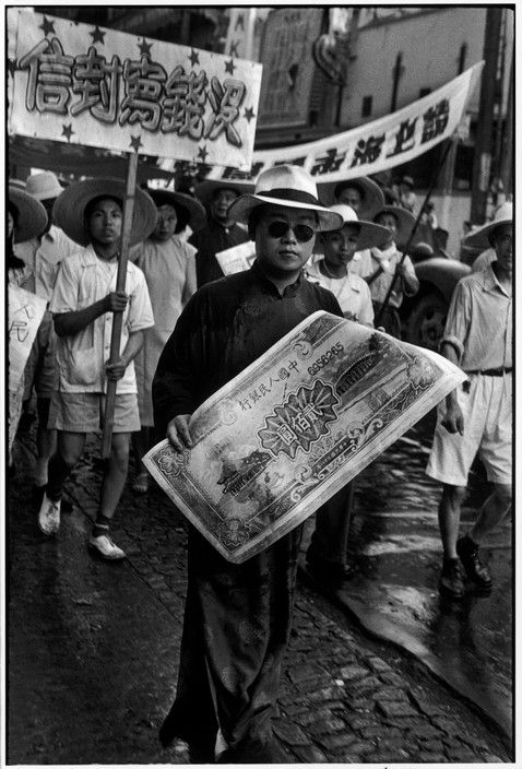 Henri Cartier-Bresson // China, 1949 -- Shanghai. A trade union representative holds the enlargement of a banknote of the new currency.