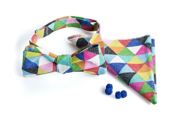 Mucha w kolorowe trójkąty - idealna dla pana młodego, na ślub, wesele i mniej zobowiązujące okazje. W komplecie poszetka oraz spinki do mankietów.  Komplet - mucha, poszetka i spinki - do kupienia w sklepie internetowym Madame Allure.