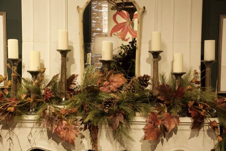 A phalanx of candles give warmth to this fall mantel at Nell Hill's.
