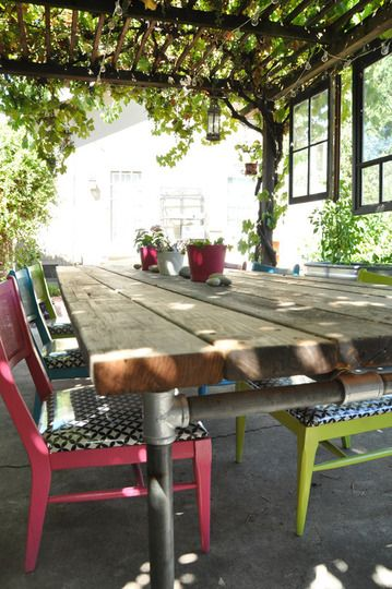Vintage windows hung from trellis, dining table made from reclaimed redwood and…