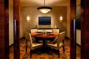 "Exclusive alcove room for small group in The Ritz-Carlton Club Lounge on the 23rd floorA communal table, small tables for two and a long bar with stools and a chalkboard column that reads ""cocktails""