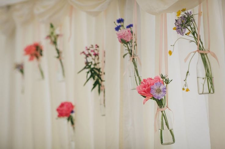 Hanging Bottles with Wild Flower Stems Wedding Decor - Helen Lisk Photography | Colourful Hanging Paper Lantern & Flower Filled Marquee Wedding | Bespoke Dresses & Tweed Suits