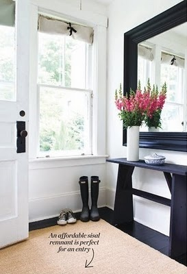 lovely entryway....love the rug, the black and the flowers