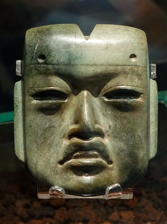 Olmec mask, c. 1200 - 400 B.C.E., jadeite, 4 x 3-3/8 x 1-1/4 inches found in offering 20 buried c. 1470 C.E. at the Aztec Templo Mayor (Museo del Templo Mayor, Mexico City)   Additional notes: Items buried in offerings included ceramic vessels, stone sculptures, obsidian blades, seashells, greenstone, and objects gathered from earlier locales (like Olmec sites and the city of Teotihuacan).