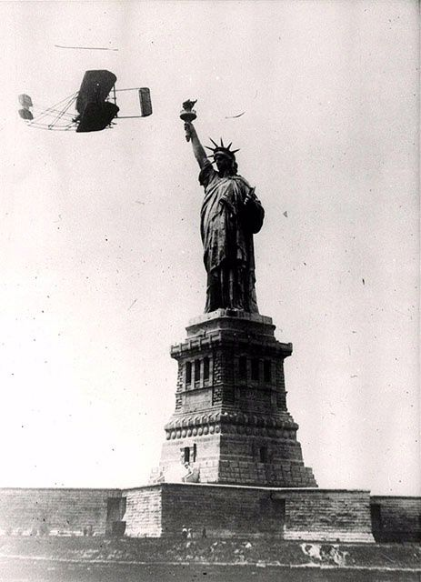 Wilbur Wright flies a Wright Model A by the Statue of Liberty during the Hudson-Fulton Celebration in 1909. The celebration was to commemorate the 300th anniversary of Henry Hudson's first entry into what was later New York Harbor as well as the centennial of Robert Fulton's first voyage of his steamboat up the Hudson River in 1809.
