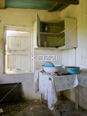 view of a dirty domestic room. - Image of a messy domestic room with utensils on table and a wooden cabinet.