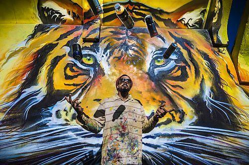France, Guadeloupe, Basse-Terre, Baie-Mahault, street art, artiste Jimmy SHEIKBOUDHOU devant une partie de sa fresque sur les murs du stade municipal  Date prise de vue : 06/11/2013 Crédit : BRUSINI Aurélien / hemis.fr