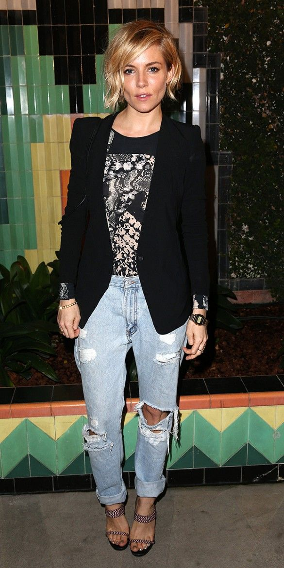 Sienna Miller dresses up ripped boyfriend jeans with a sleek black blazer, printed blouse, and strappy heels