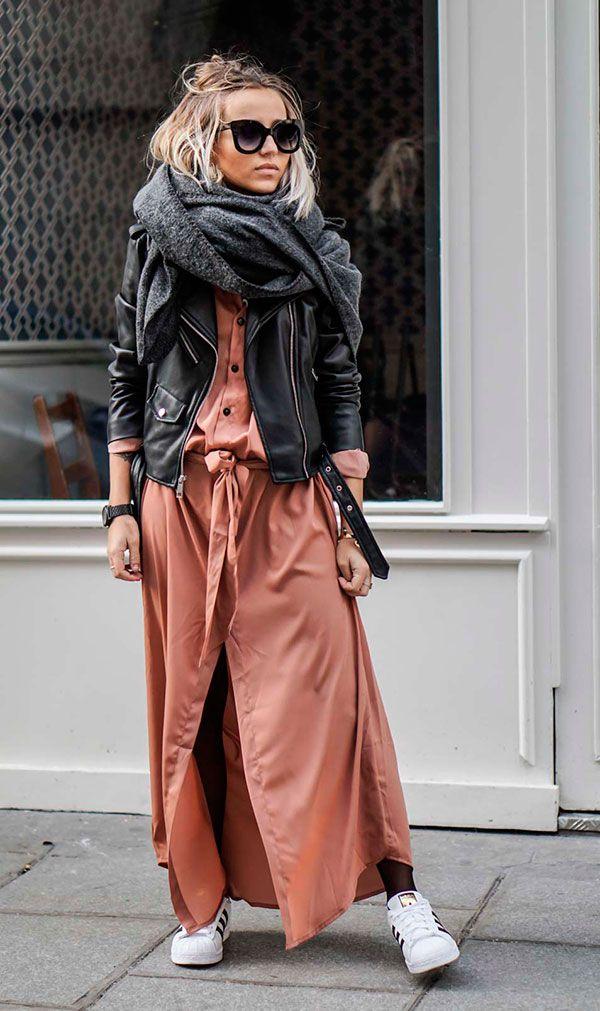 Street style look com sobreposições de vestido, cachecol, e jaqueta couro com tênis branco.