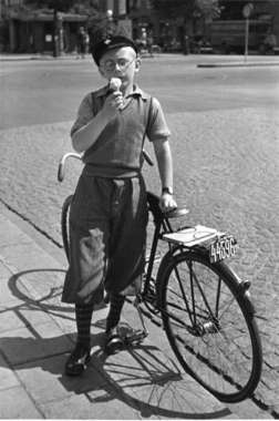 1935. Digitalt Museum - En pojke i golfbyxor, pullover och skärmmössa äter glass vid en cykel. Fotograf: Gunnar Lundh